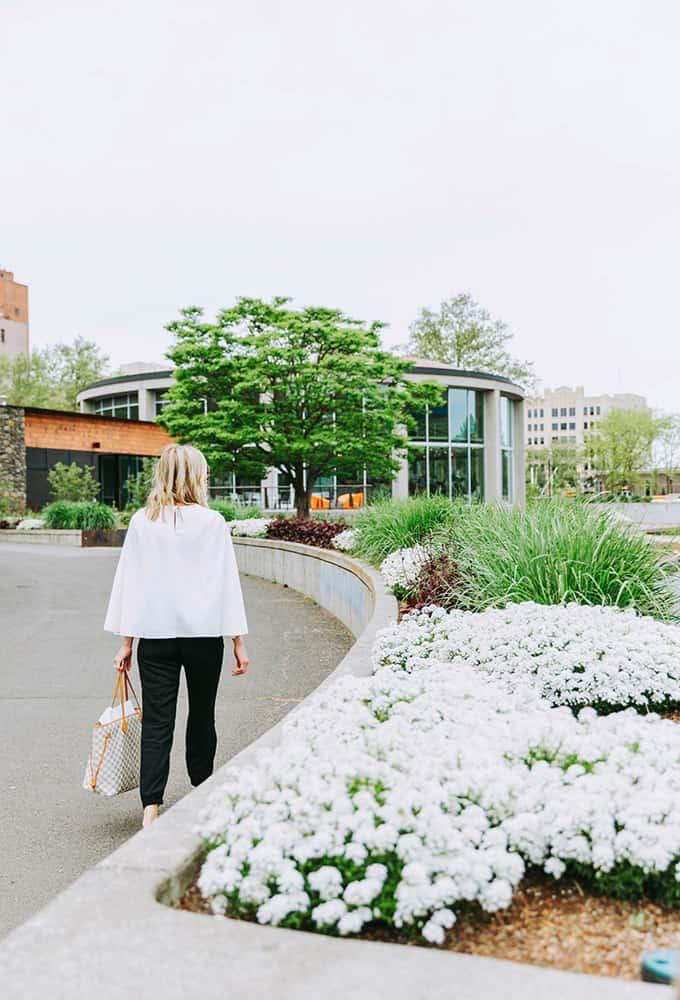 Women walking to building by flowers | Davenport Centennial