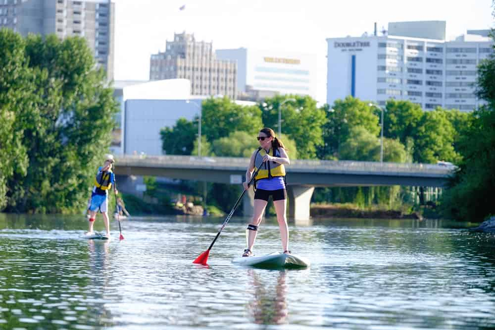 Couple Paddle Boarding on River | Davenport Centennial