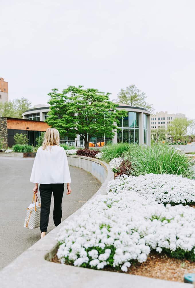 Women walking towards building by flowers